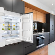 Interior photo of kitchen with open french door refrigerator, modern minimalist cabinets and gas range cook top