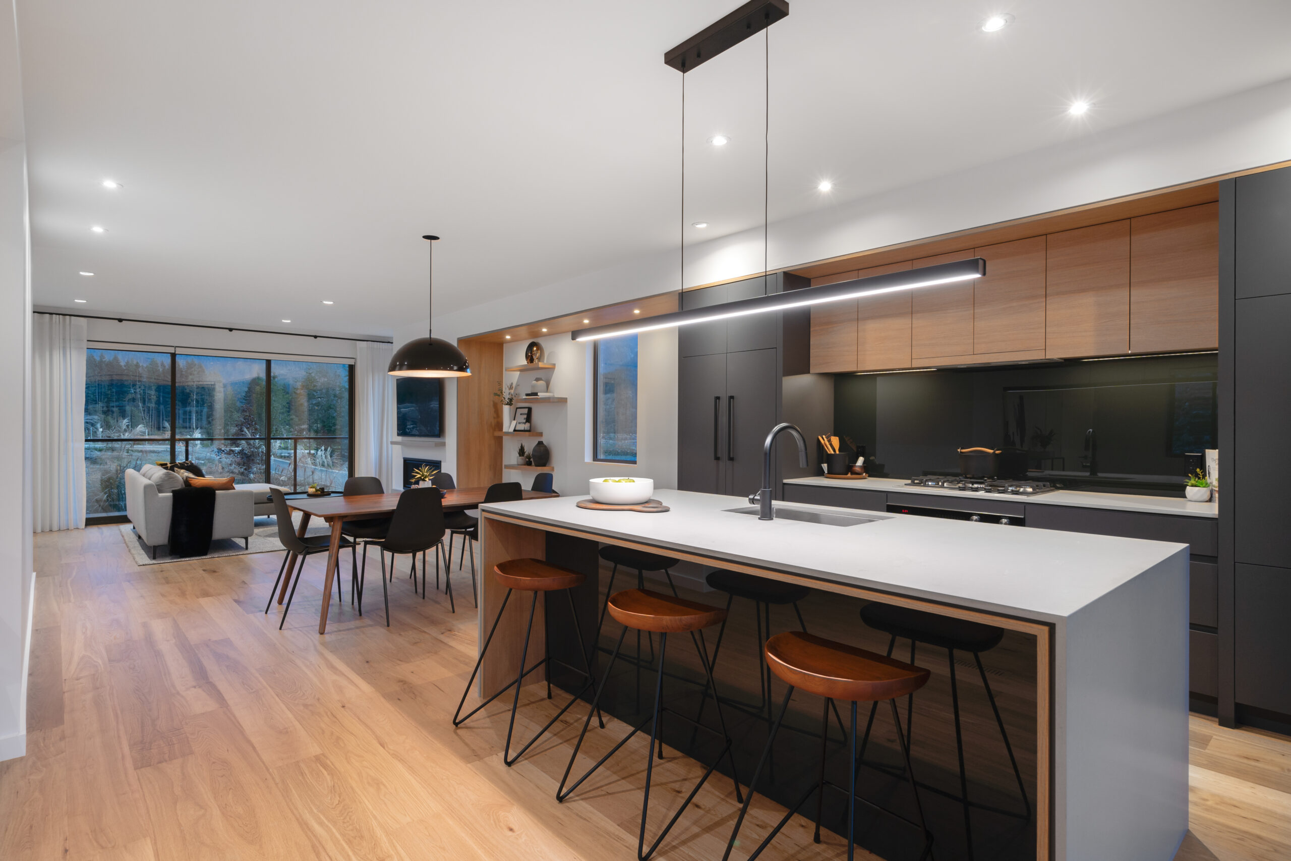 Picture of open concept living room and kitchen with modern kitchen island with linear designer pendant light, and clean minimalist cabinets