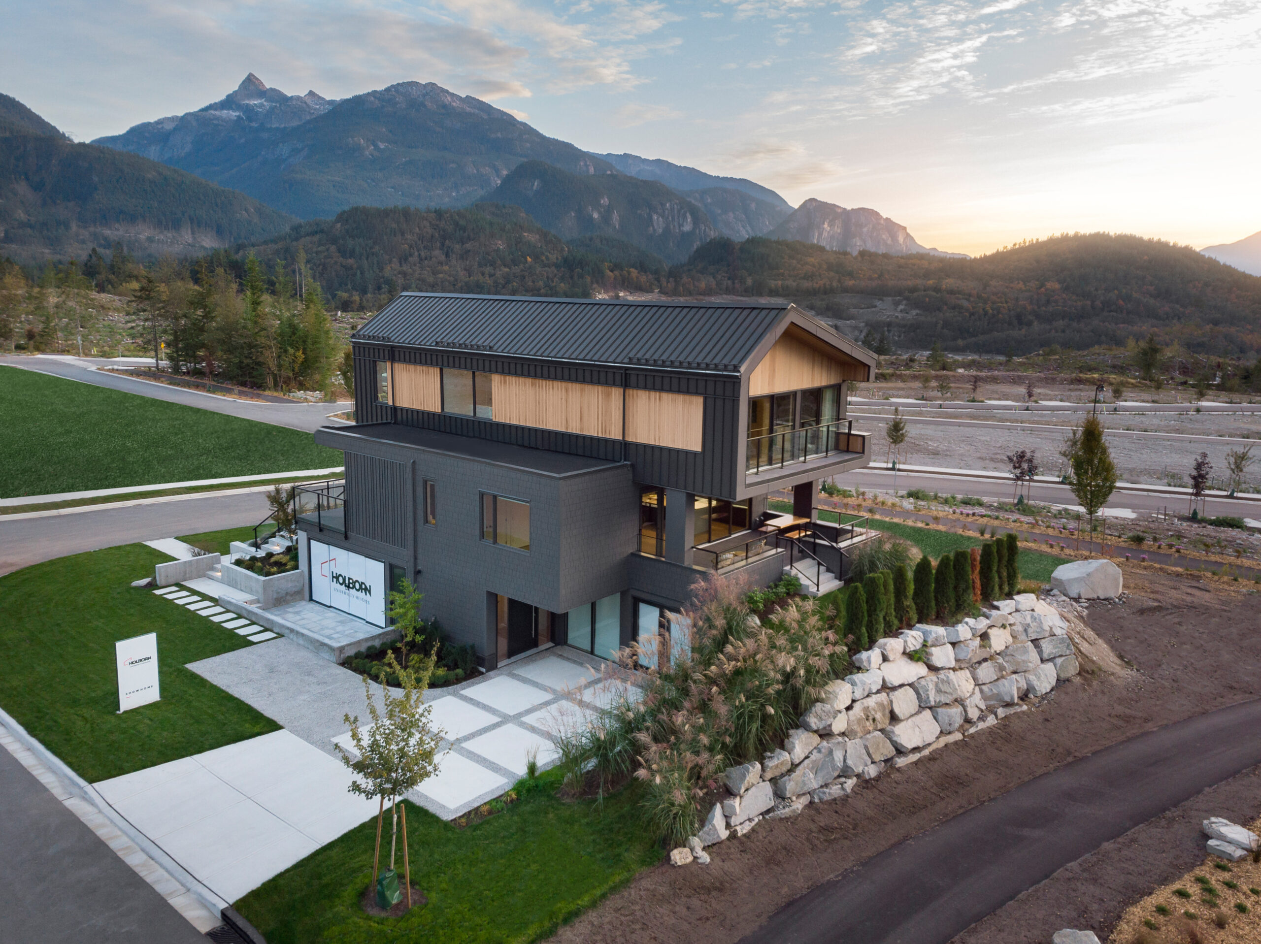 Aerial View of Dark Exterior Show Home and Mountain Range in background