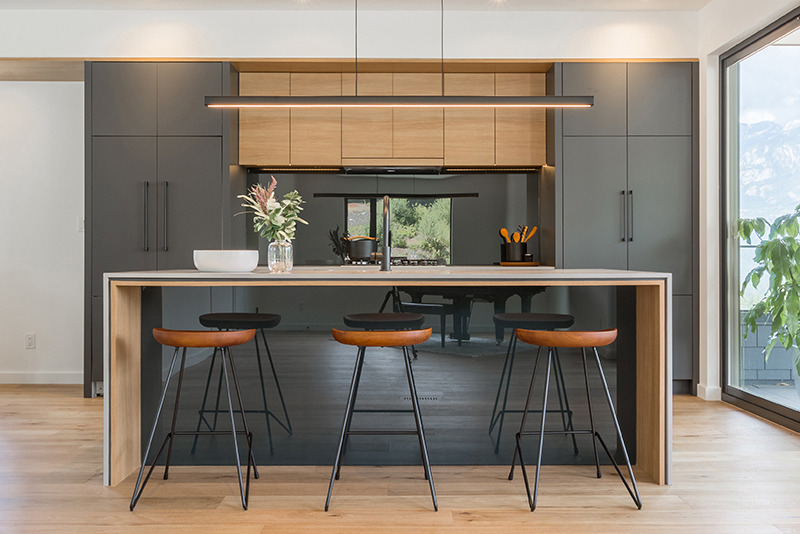 Picture of kitchen facing the modern central island with linear pendant light above