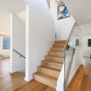 Picture of central staircase with wood flooring to contrast walls and metal railings with clear glass
