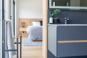 Picture view of master bedroom bed and nightstand from left corner of ensuite floating vanity.