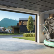 Rendering of double car garage with bicycles, kayak and other sporting goods hanging on wall. A luxury sedan is parked on the driveway.
